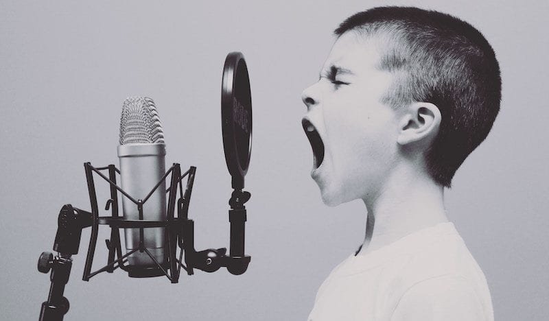 boy speaking into microphone